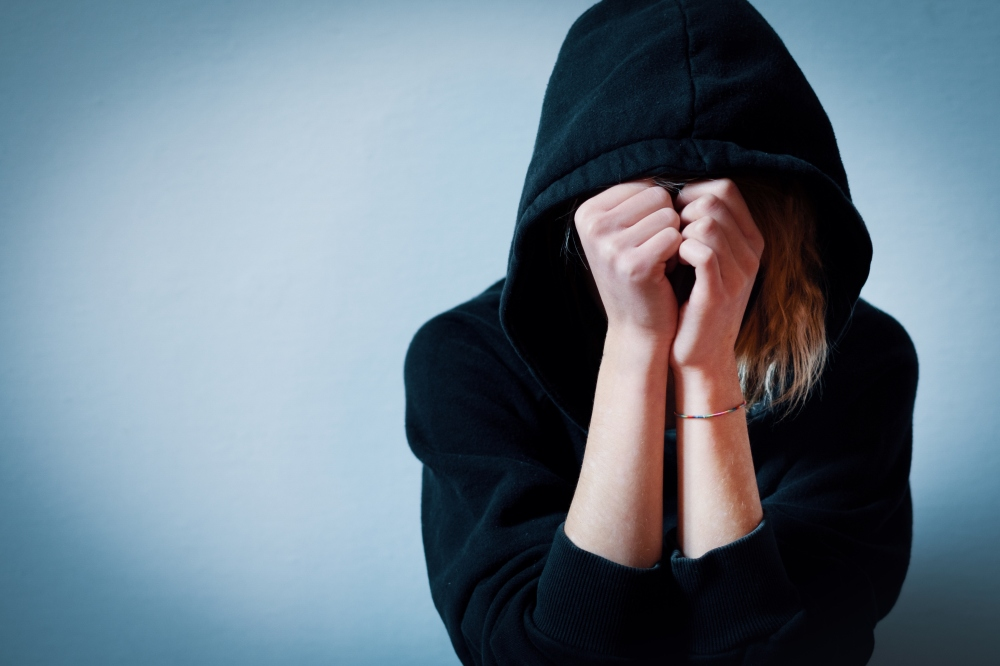 Young girl hiding her face under hooded sweatshirt isolated on b